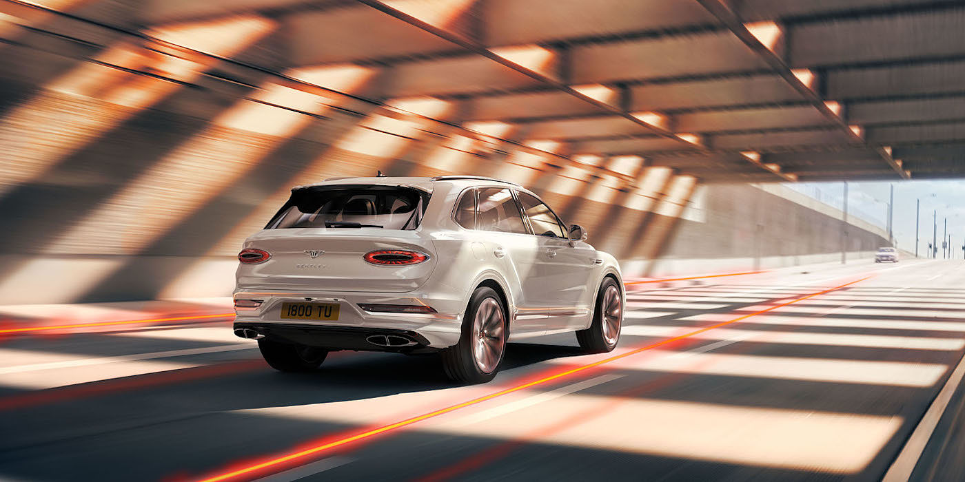new-bentley-bentayga-hybrid-in-ice-white-paint-rear-three-quarter-driving-in-tunnel-los-angeles